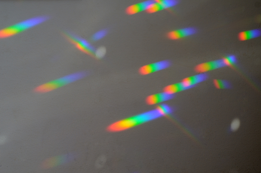 Rainbows on the wall, from glass prisms in the window.