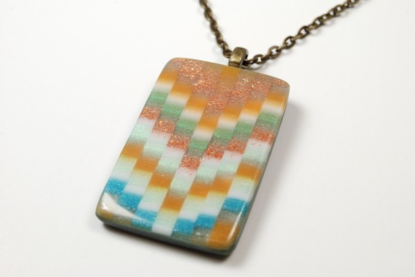 Sunset orange and sage green polymer clay pendant created with a bargello effect.