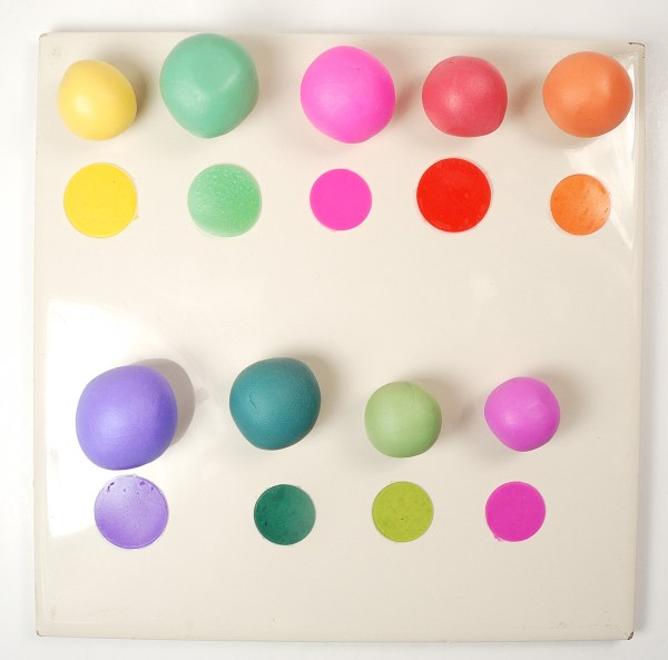 Balls of unbaked polymer clay tinted with alcohol ink are compared against baked clay to show the color difference.
