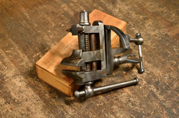 French bench mounted rotating jeweler's vise with small anvil.