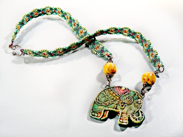 Bohemian Behomoth, a necklace made with micro macrame and a polymer clay elephant.