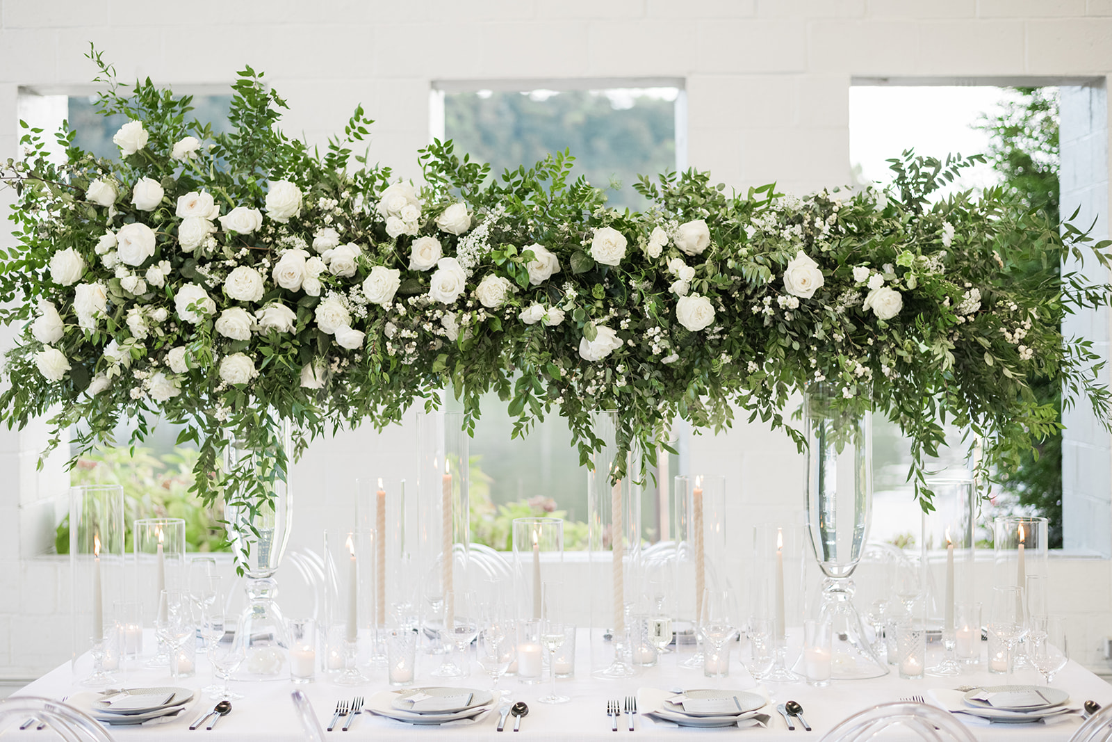 tall greenery white wedding reception table centerpiece candles riverfront weddings Levana Melamed photography Soiree by Souleret