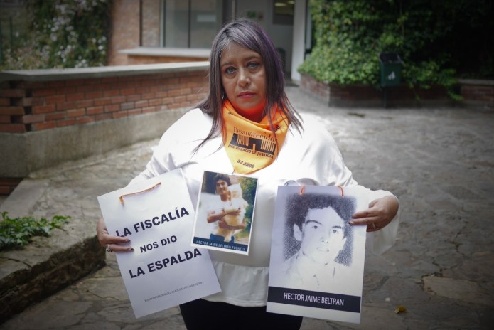Seeking justice: Pilar Navarrete with photos of her husband who was a waiter in the Palacio de Justicia café in November 1985 during the siege.