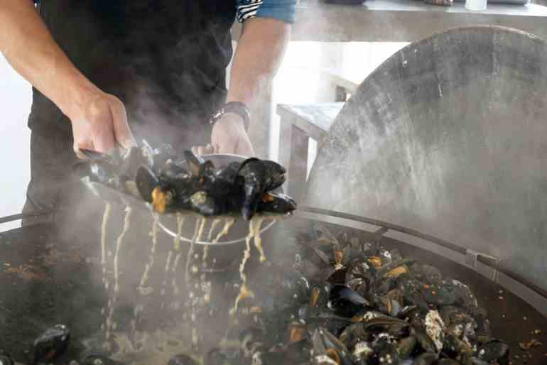 The broth drips from mussels just cooked on a large pan and being transferred to a bowl