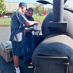 AJ preparing meat for smoking in big smoker