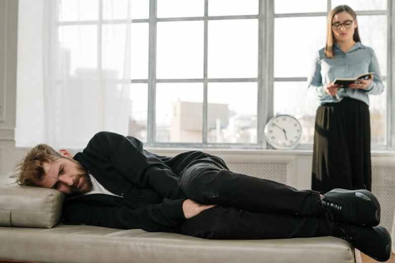 man in black jacket lying on bed