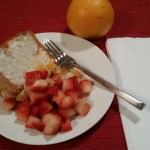 Close in view of plated slice with strawberries and an orange in the background