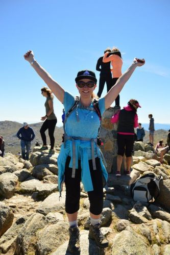 woman with arms up at summit of mount kosciuszko australia