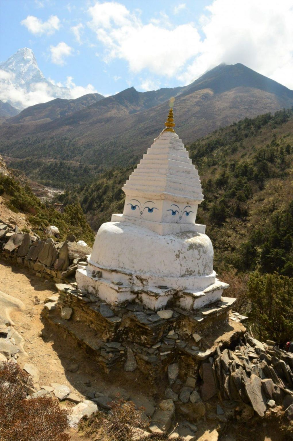 white stupa on everest base camp trek with mountains in background