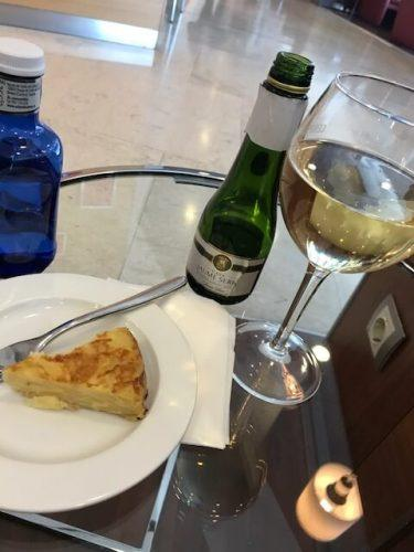 glass of cava and plate with tortilla at iberia business class lounge madrid airport