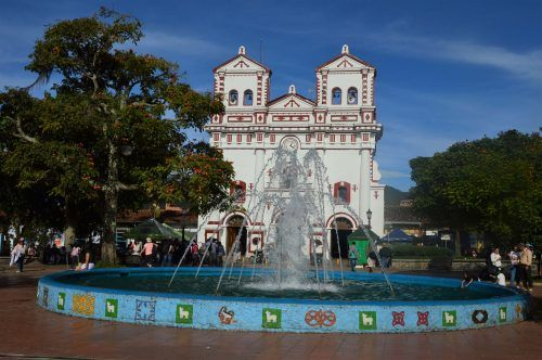 Colourful church with colourful fountain guatape