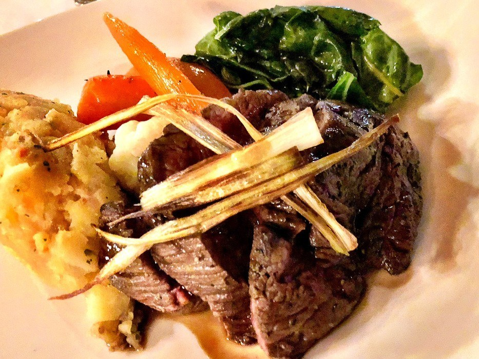 steak with potato and greens and carrots on a white plate at kwandwe