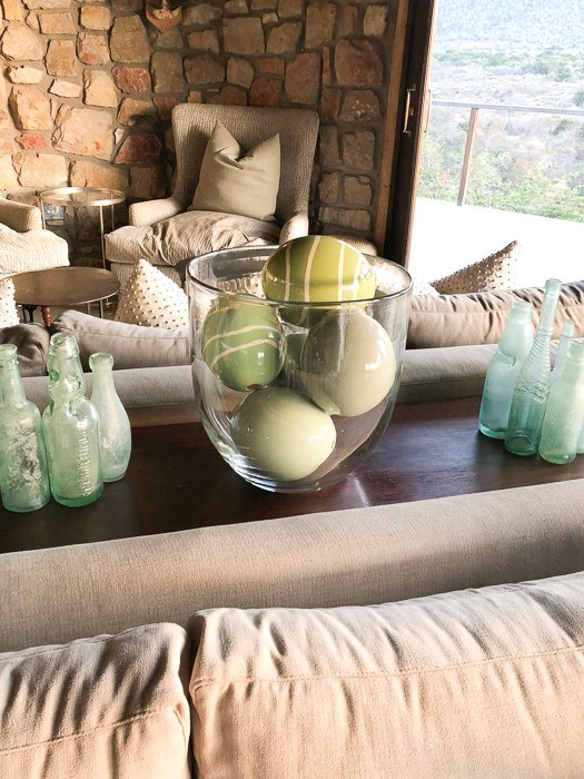 green ostrich eggs in a glass vase in a living room at kwandwe