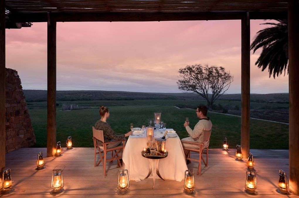 couple having dinner on an open deck with lots of lanterns in south africa