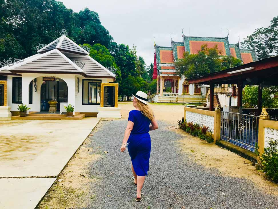 woman in hat from behind with thai temples