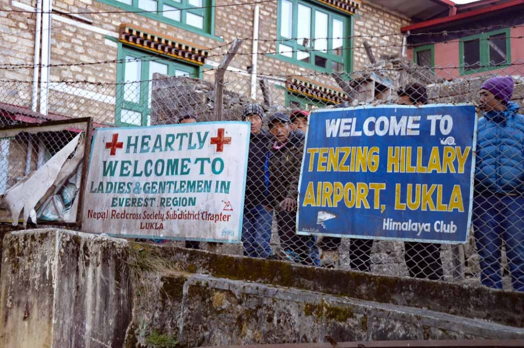 signs against railing at lukla airport on my everest base camp trek blog