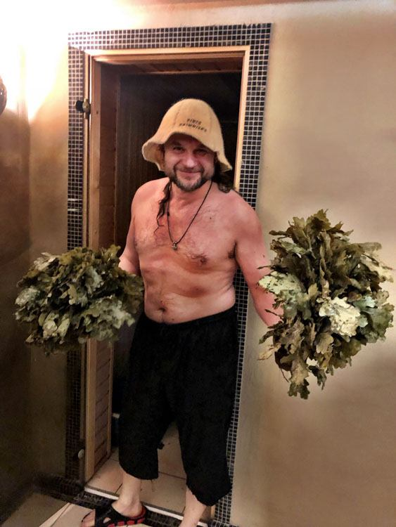 Man with birch branches for whisking outside a sauna