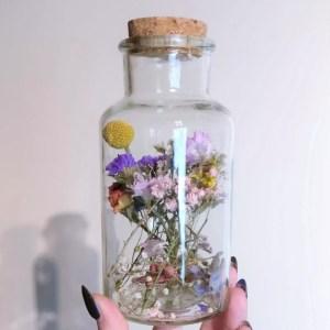 Gedroogde bloemen in medicijnenfles