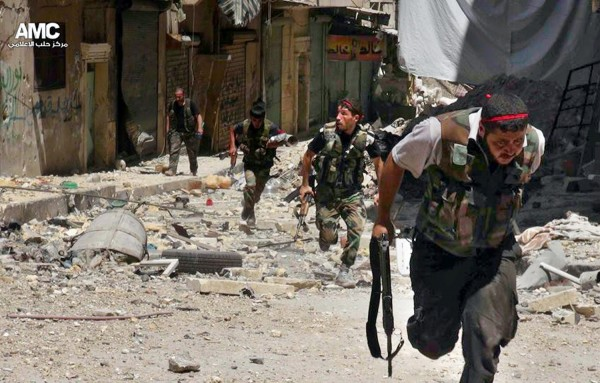 A publicly distributed picture from the Aleppo Media Centre shows rebel fighters evading government troops [AMC via AP]