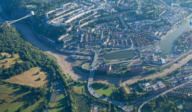 The Western Harbour from above, with fields on the other side of the River Avon, the Clifton Suspension Bridge, and Cumberland Basin Road network.