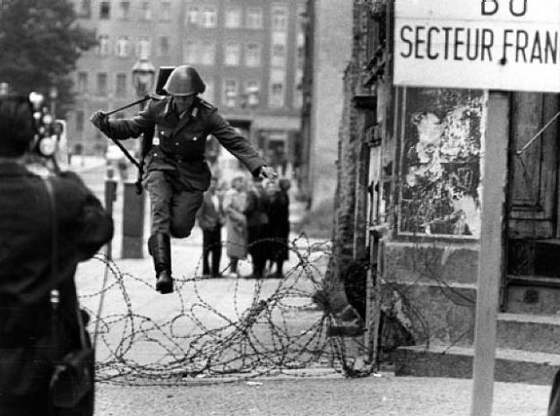 19-year-old guard Conrad Schumann on August 15, 1961 jumping over the barbed wire in his uniform while toting his machine gun. Photo@ artwork images - Klaus Lehnartz.