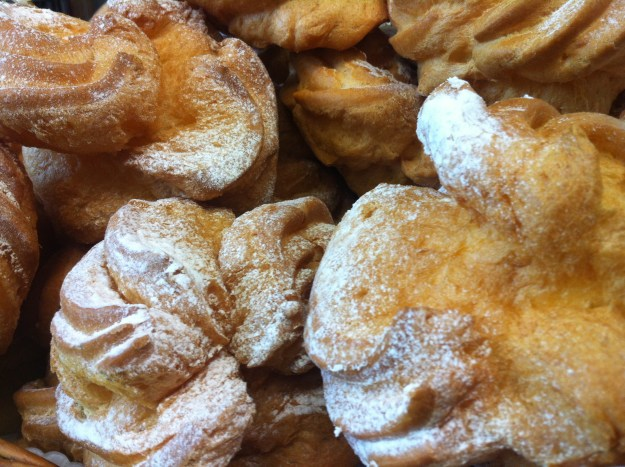 Sugary puffs filled with clotted custard cream and covered with castor sugar in Riga, Latvia.