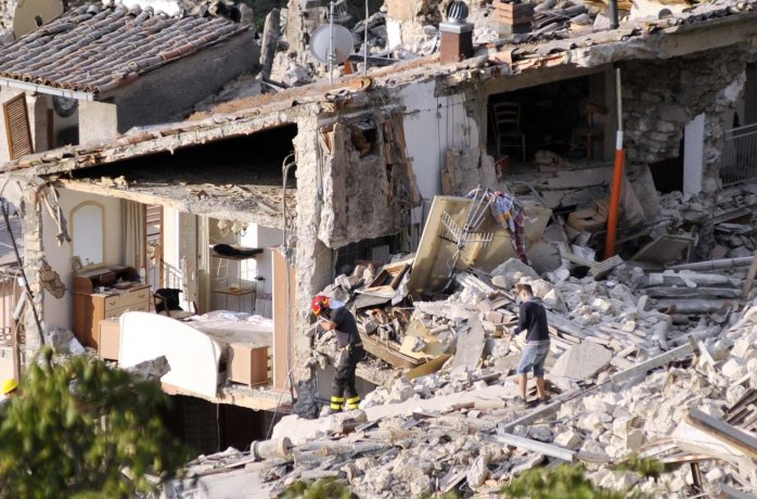 Members of an emergency team walking on the rubble of collapsed buildings in Pescara del Tronto, Italy. ©Cristiano Chiodi - EPA