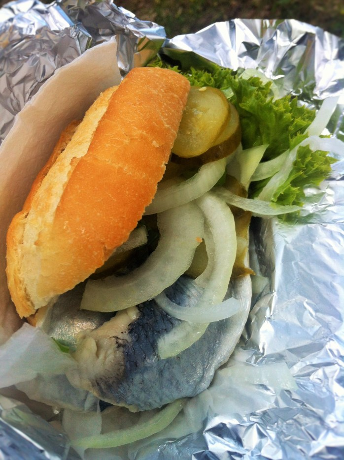 My fish bun (Fischbrötchen) made with pickled or Bismarck herring served on kitchen foil in a bread bun (brötchen) with pickles, lettuce and huge slices of fresh raw onions!