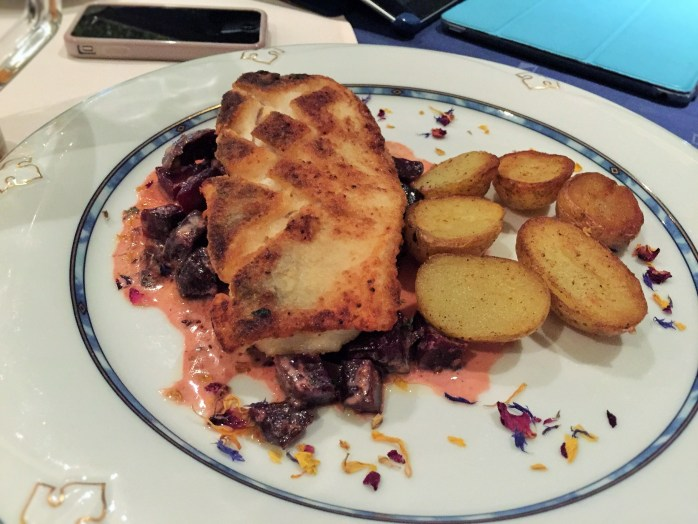 Breaded fish over marinated beetroot chunks in a sauce, served with roast potatoes sprinkled with edible flowers. ©The Music Producer - Frank Böster