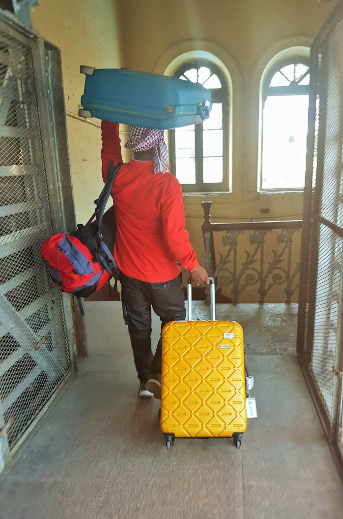 Coolies / porters carrying luggage at the train station in India; porters; Indian porters; Indian luggage; transport; train station