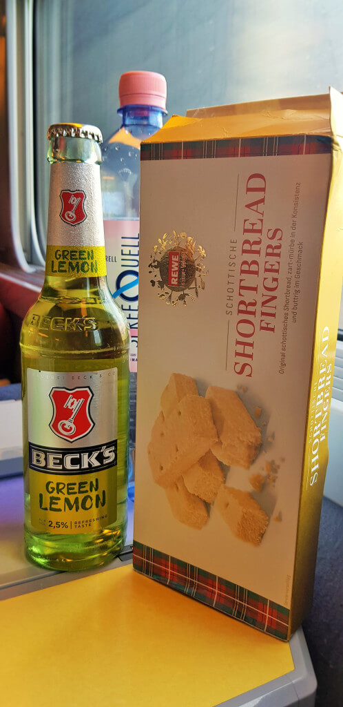 Take some refreshments with you when travelling on a European train; refreshments; snacks; beer, bier; German beer; German drink; Beck's beer; Becks beer; Beck's green lemon; green lemon; green lemon beer; shandy beer; shandy; water; a bottle of beer; Beck's; Becks; shortbread fingers; shortbread biscuits; shortbread; biscuits; food and drink; drink; food; eat; how to use the train in Europe 2019: 10 tips to help you; how to use the train in Europe: 10 tips to help you; how to use the train in Europe; how to use the train in Europe 2019; how to use the train; how to use the European train; how to use Deutsche Bahn; how to use the European railway; how to use the railway; how to use the German train; how to use the Polish train; how to use the Hungarian train; how to use the French train; how to use the Czech train; how to use the Spanish train; how to use the UK train; how to use British trains; how to use trains in the UK; how to use trains in Britain; how to buy train tickets; how to buy train tickets on European trains; how to buy train tickets in Europe; how to get on the train; 10 tips to help you; tips to help you, a train guide; a railway guide; a European train guide; a European railway guide; taking the train in Europe; train station; station; railway; European train; train; trains in Europe; European railway; at the railway; long train journey; train travel; travel by train; travel; European; Europe;