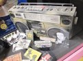 Boobmbox e cassette di Simonon del 1982. A sinistra una foto della band scattata da Patti Smith, colorata a mano da Simonon