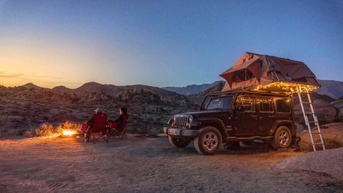 Camping on top of a jeep with backpacking gear