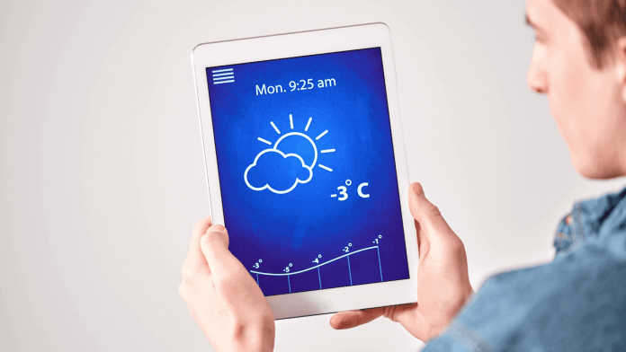 a man is checking weather forecast on a device