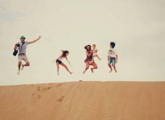a family of 5 jumping on a sand dune in summer vacation