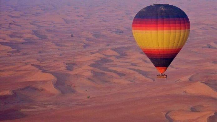 hot air balloon on golden dunes of Arabia