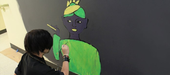 Zach Graves paints his interpretation of Zora Neil Herston during the Mural Painting Course.