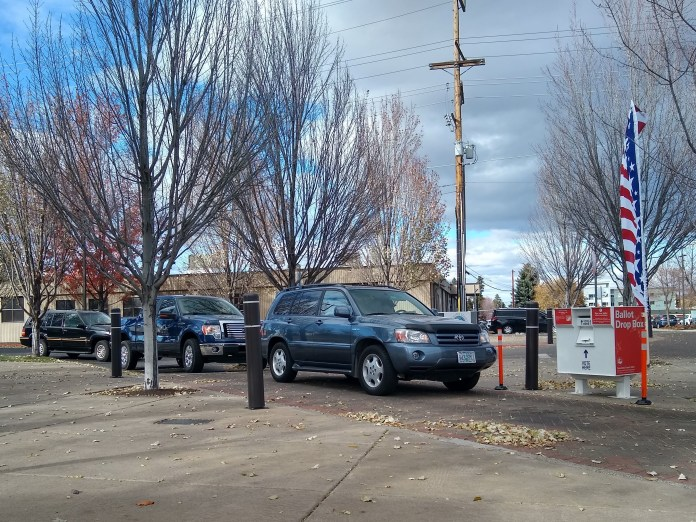 A line of cars waits to vote in the 2020 general election in Bend, Oregon, on a cloudy day downtown, onthings including ballot measures, presidential and local candidates, and taxes.