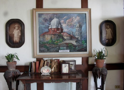 A painting of San Sebastian Cathedral along with other vintage furnitures and frames.
