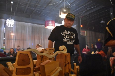One of the guys from IBake Denver looks at some of the wooden pipes for sale.