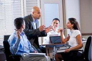 Confident Hispanic manager meeting with office workers