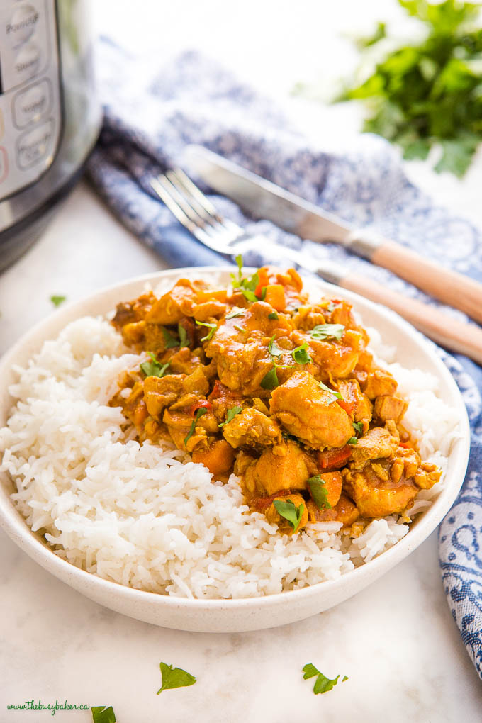 butter chicken over rice in a white bowl