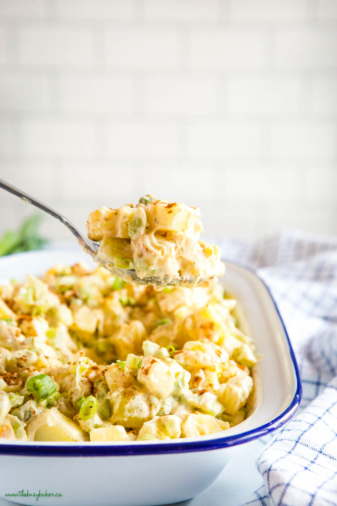 spoonful of potato salad with green onions and paprika