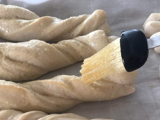 easy homemade breadsticks being brushed with butter and sprinkled with garlic seasoning