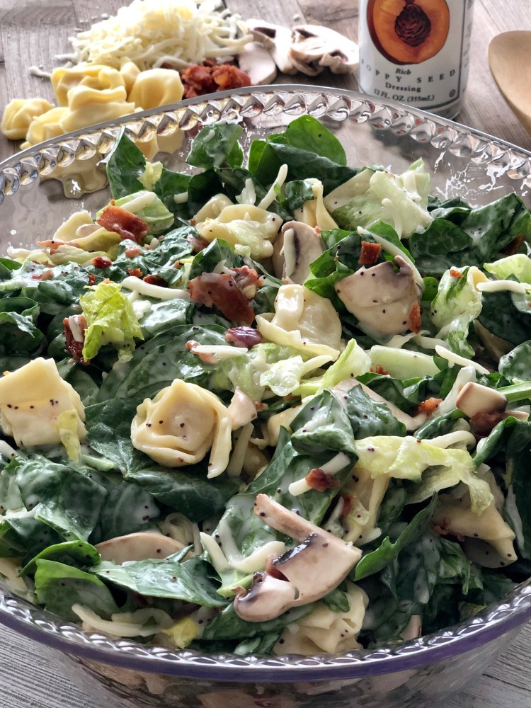 spinach tortellini salad om a bowl with poppy seed dressing
