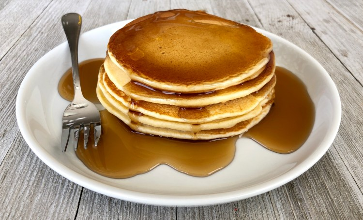 the Best Homemade pancakes on a plate with maple syrup on them