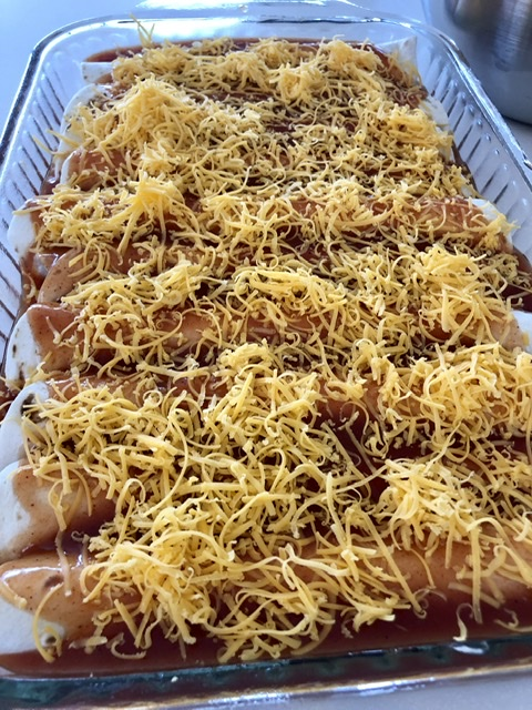 9x13 pan of rolled up chicken enchiladas covered in red enchilada sauce and shredded cheddar cheese