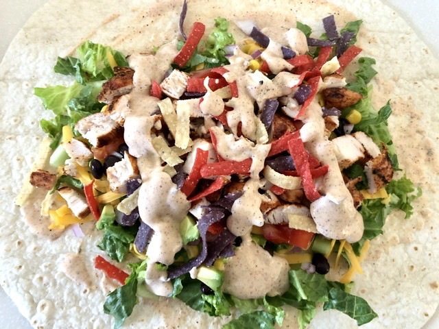 Southwest Chicken Sandwich Wrap with lettuce, chicken, tomatoes, black beans, corn, avocado,red onions, tortilla strips and taco-ranch dressing in the center of a large flour tortilla