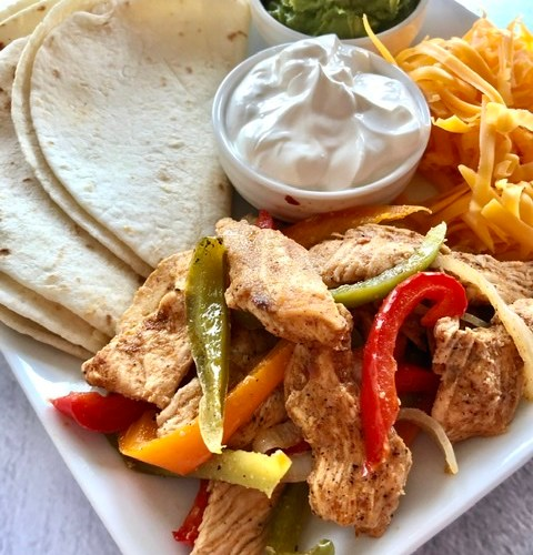 Easy Sheet Pan Chicken Fajitas served with flour tortillas, peppers, onions, sour cream and guacamole