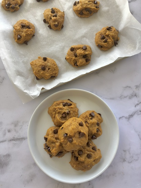 Pumpkin Chocolate Chip Cookies stacked  on a plate and just baked on a half sheet baking pan
